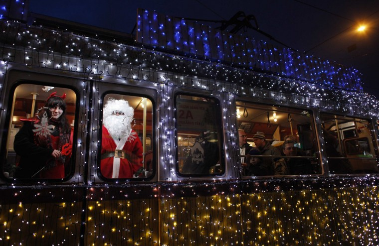 A man dressed as Santa Claus and a woman dressed as mythical creature Krampus travel in a tram decorated with Christmas lights in the centre of Budapest December 3, 2010. (Laszlo Balogh/Reuters)