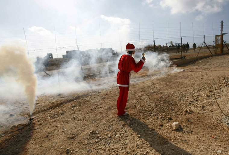 A Palestinian demonstrator dressed in a Santa Claus costume stands near a teargas canister fired by Israeli troops during a protest against the controversial Israeli barrier in the West Bank village of Bilin near Ramallah December 24, 2010. (Mohamad Torokman/Reuters)