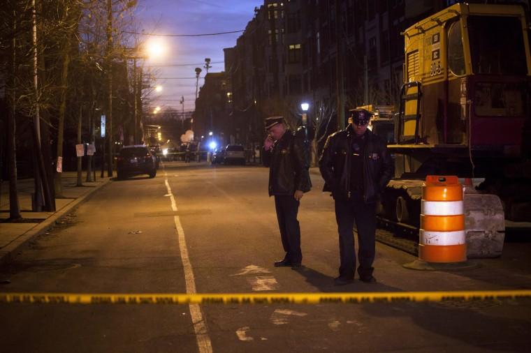 Сотрудники правоохранительных органов следить за сцену за пределами квартиры по 1313 Grand Street, считал, должен быть подключен к стрельбу в школе Коннектикута элементарных в Хобокен, Нью-Джерси.  По имеющимся данным, насчитывается 27 погибших, включая 20 детей, после боевик открыл огонь по крайней Sandy Hook начальной школы в Newtown, Коннектикут.  Стрелок, идентифицированный как Адам Ланца, также был найден мертвым на месте происшествия.  (Michael Nagle / Getty Images)
