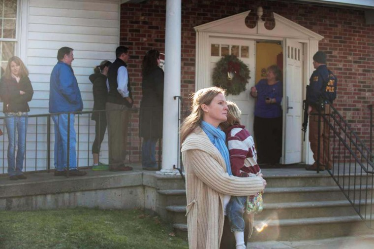 A woman holds a child as people line up to enter the Newtown Methodist Church near the the scene of an elementary school shooting on December 14, 2012 in Newtown, Connecticut. According to reports, there are about 27 dead, 18 children, after a gunman opened fire in at the Sandy Hook Elementary School. The shooter was also killed. (Douglas Healey/Getty Images)