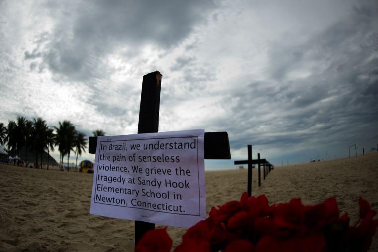 Бразильская ассоциация Рио-де-Пас (Рио мира) отдали дань памяти жертвам Sandy Hook Элементарные съемки школа на пляже Копакабана в Рио-де-Жанейро 15 декабря 2012 года.  Мировые лидеры выразили шок и ужас после боевик убиты 20 детей в съемках Коннектикут.  (Christophe Simon / AFP / Getty Images)