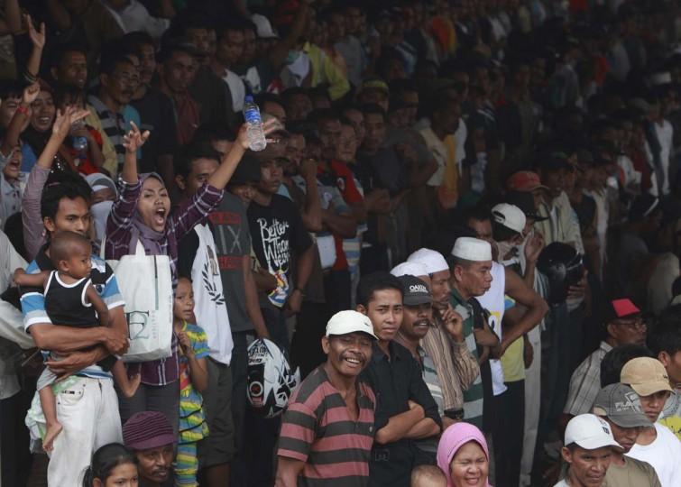 Зрители поднять во время гонки на ипподроме Panda, вне Бима, 18 ноября 2012 года.  С участием около 600 лошадей, скачки происходят вокруг пыльно, овальный трек около одной мили.  Фото сделано 18 ноября 2012.  (Beawiharta / Reuters)
