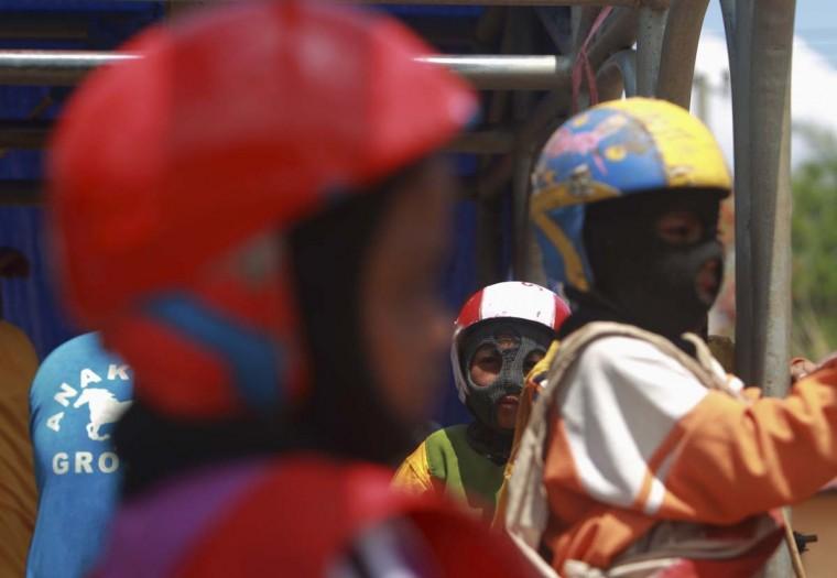 Ребенка жокеев сидеть в стартовые ворота перед гонкой на трассе за пределами Бима, 18 ноября 2012 года.  (Beawiharta / Reuters)