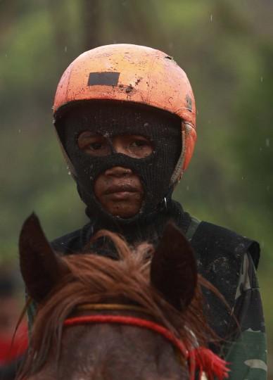 Ребенок жокей сидит на коне после гонки на ипподроме Panda вне Бима.  Председатель организационной группы рас », Хаджи Sukri, отрицает, что есть какая-то опасность для детей, говоря, что они все умелые всадники, и ни один не был убит или серьезно не пострадал.  Фото сделано 18 ноября 2012.  (Beawiharta / Reuters)