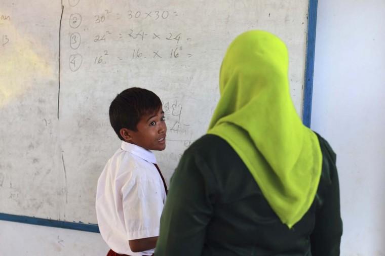 Endiansyah Мохаммад (L) говорит своему учителю во время урока в Dompu.  Десятки ребенка жокеев, некоторые в возрасте восьми-летний принять участие в гонках.  Фото сделано 20 ноября 2012.  (Beawiharta / Reuters)
