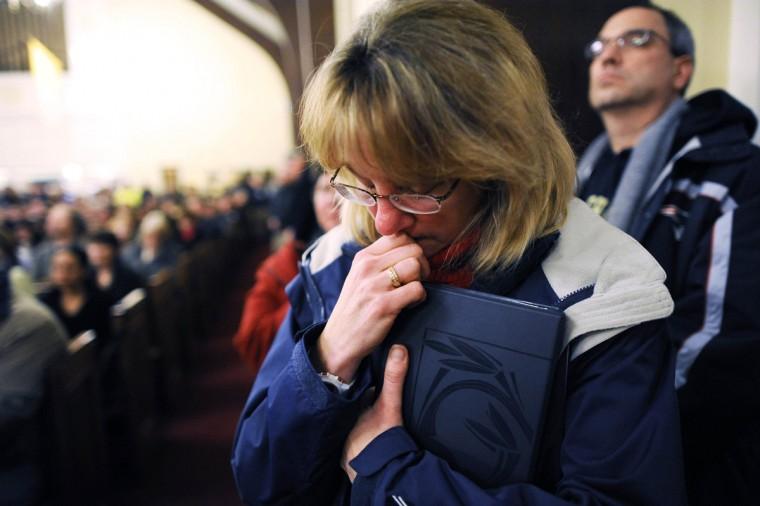 Скорбящих собрались в Санкт-Роза Лимы Римско-католической церкви на всенощной для жертв Sandy Hook Элементарные съемки школы, которые оставили по меньшей мере 27 человек погибли - многие из них детей - в Newtown, Коннектикут.  (Andrew Gombert / Pool)