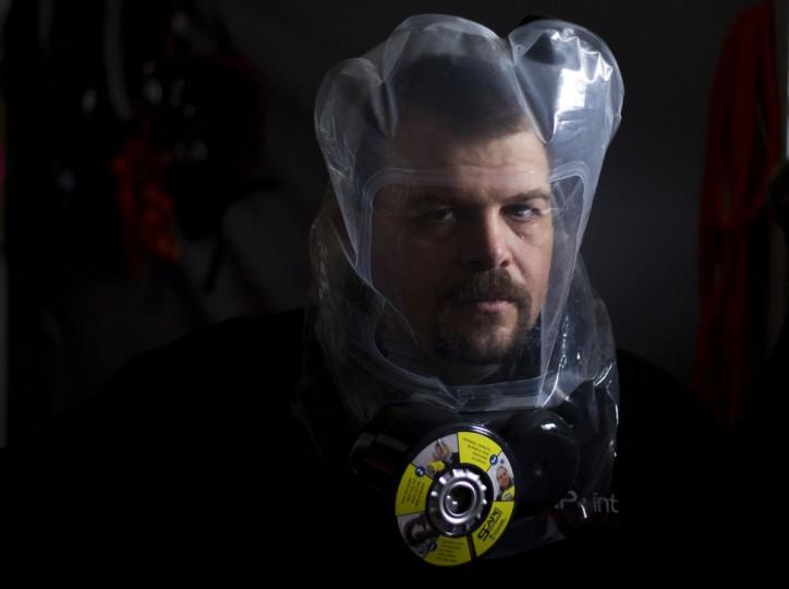 """Phil Burns демонстрирует очистки воздуха пейзаж маски в своем доме в American Fork, штат Юта, 14 декабря 2012 года.  Бернс является частью """"prepper"""" движение, группа людей, активно готовится к чрезвычайным ситуациям.  Хотя большинство preppers скидка пророчество майя конец света календарь, многие по-прежнему готовится к потенциальной катастрофы в конце года подходах.  (Jim Urquhart / Reuters)"""