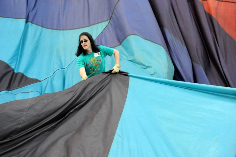 "Cheryl Hughes positions the fabric of ""Blue Dragon,"" a hot air balloon owned by Jack Edling. (Kim Hairston/Baltimore Sun)"