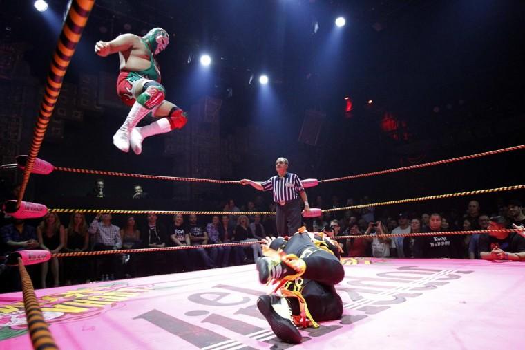 Луча Либре борец Доктор Maldad (L) прыгает в воздухе, борясь против члена сумасшедшим курам во время шоу Lucha Vavoom как часть Синко де Майо празднования в майя театр в Лос-Анджелесе, Калифорния 5 мая 2013. (Mario Anzuoni / Reuters)
