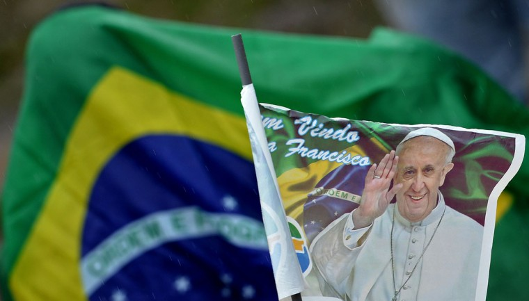 A faithful holds a flag with an image of Pope Francis as the pontiff speaks from a stage mounted on a football field at the Varginha favela in Rio de Janeiro, on July 25, 2013. The Varginha favela is a community of 1,000 people which for decades was under the sway of narco-traffickers until it came under police control less than a year ago. (Tasso Marcelo/AFP/Getty Images)