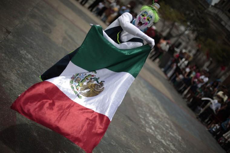 Клоун держит Мексиканский флаг во время парада чтобы открыть Конвенцию 5-й ежегодный клоунов в городе Гватемала.  (Jorge Dan Lopez / Reuters фото)