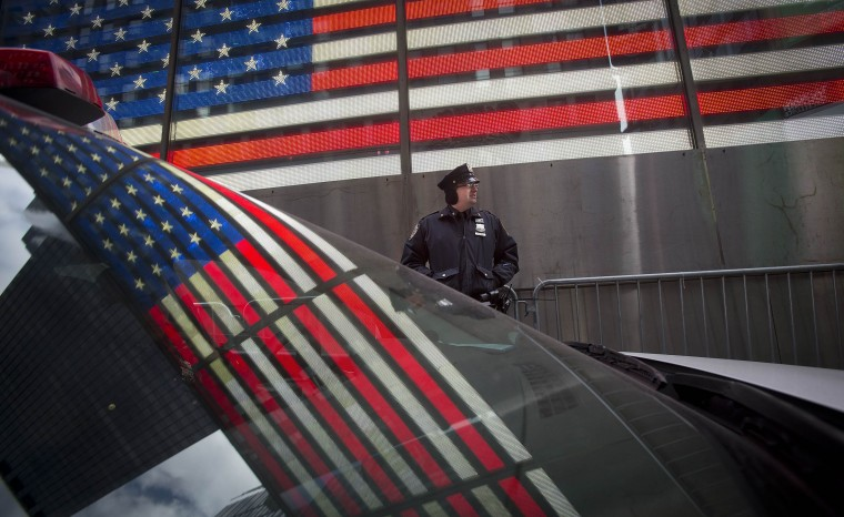 Baltimore Sun caption: The U.S. flag is reflected in the window of a police car as a police man stands guard in Times Square ahead of New Year's Eve celebrations in New York, December 31, 2013. Security has been stepped up in the area around where the celebrations will take place. (REUTERS/Carlo Allegri)