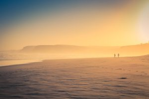 ocean sunset with pastel colours and silhouetted people and cliffs