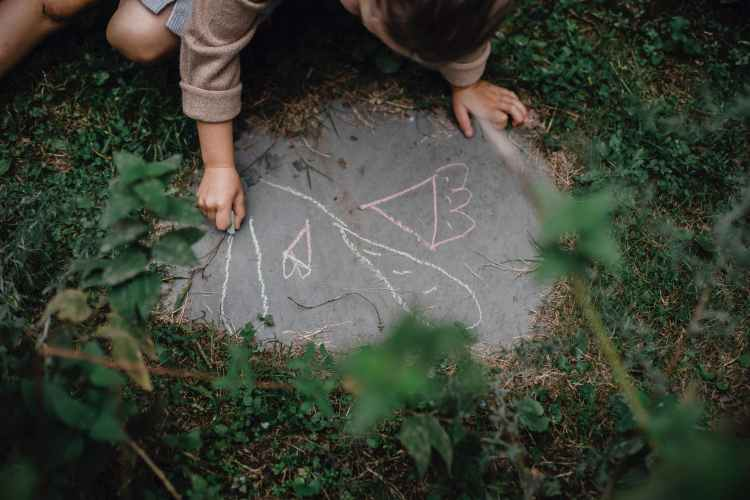 child drawing picture on concrete block in grassy yard