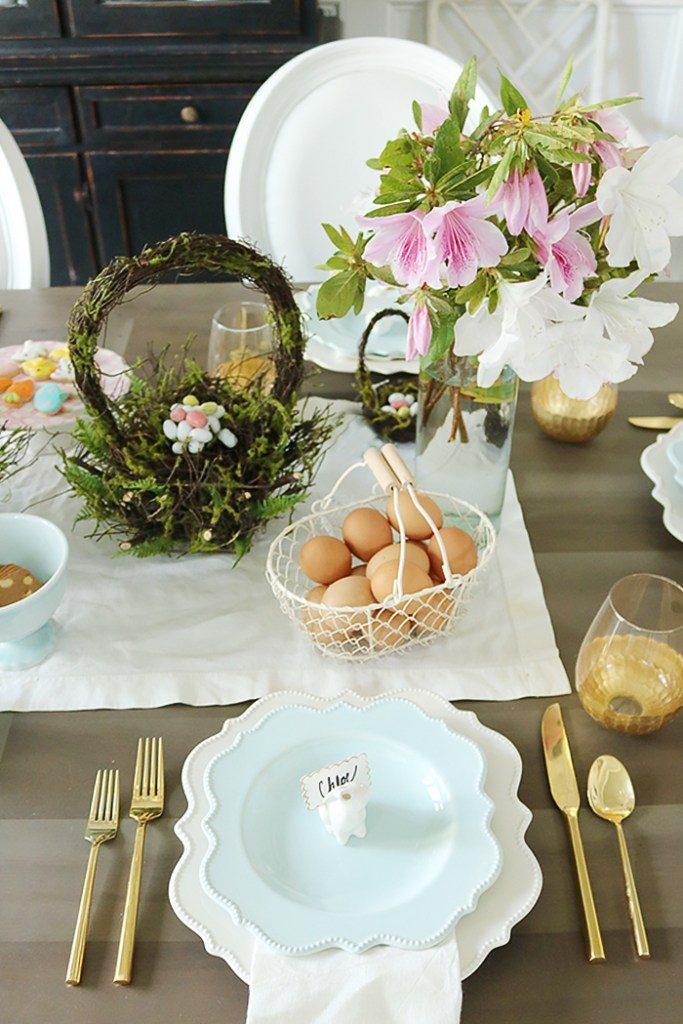 easter tablescape using flower branches, easter table decorations, floral centerpieces, flower branches centerpieces, natural, simple easter tables, flower garland, moss basket, easter eggs, bunny place setting, blue plates, scallop plates