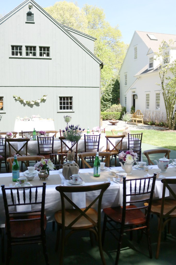 Mother's Day Garden tea party table decor setting with tea cups and tea pots with flowers. Simple outdoor garden tea party decorations with a white house and barn in a New England Connecticut living || Darling Darleen
