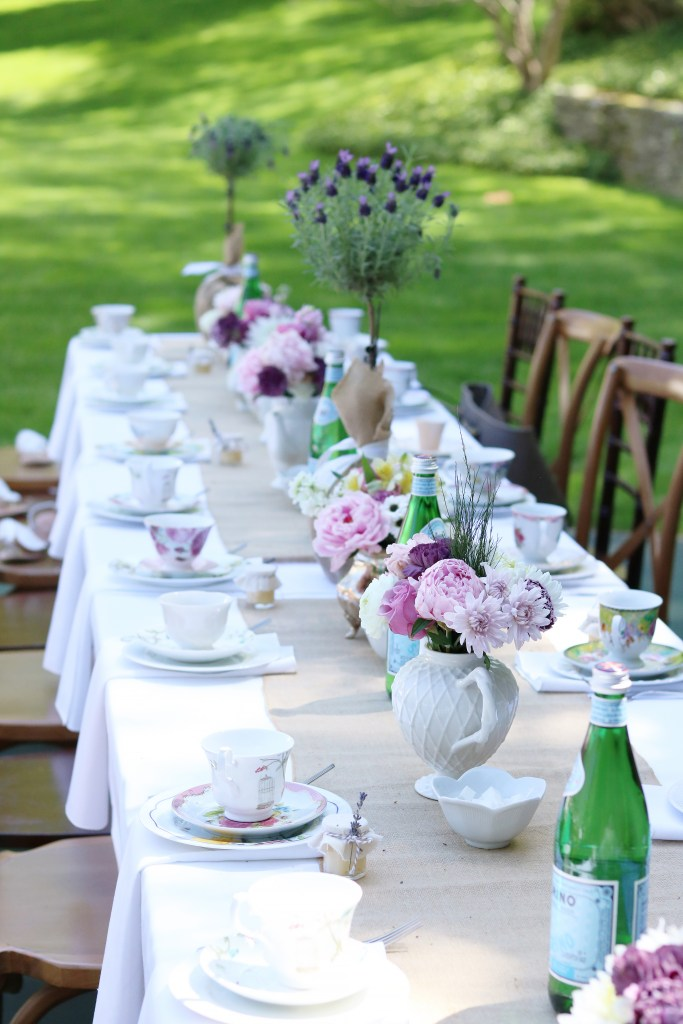 Mother's Day Garden tea party table decor setting with tea cups and tea pots with flowers. Simple outdoor garden tea party decorations || Darling Darleen