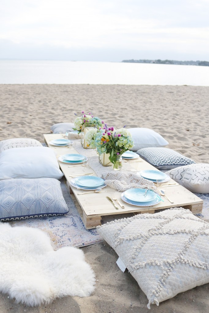 Boho Birthday Beach dinner with pillows and vintage rugs.  Set up plates and table decor on pallet and add pillows.  Birthday Beach dinner idea, beach dinner casual, lanterns and candles || Darling Darleen