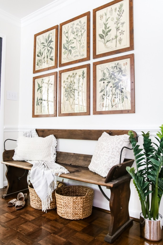 Wooden bench in a hallway with botanical prints hung above on the wall