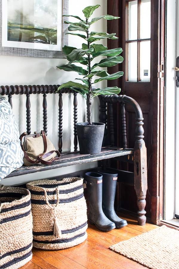 Black spindle back bench with baskets and rubber boots underneath