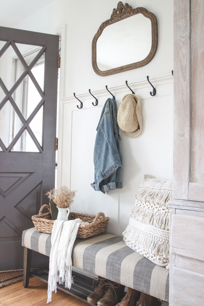 Entryway with gray door, a gray and white upholstered bench. A row of hooks hangs above the bench.
