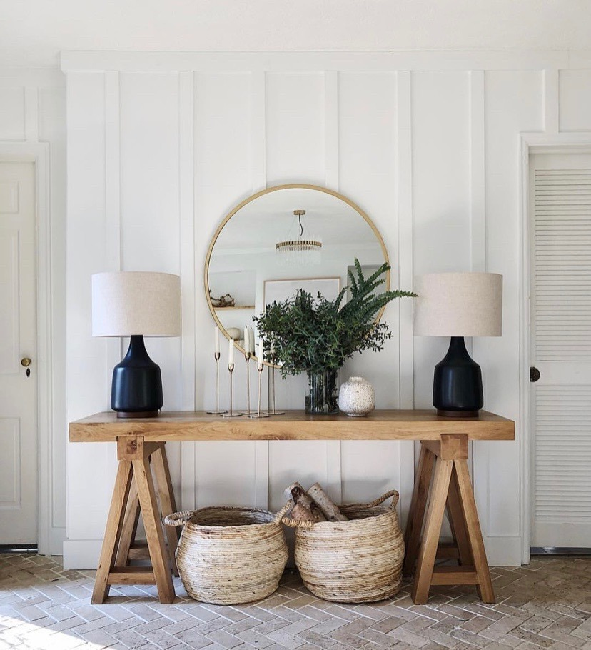 Entryway console table with lamps on top and baskets underneath