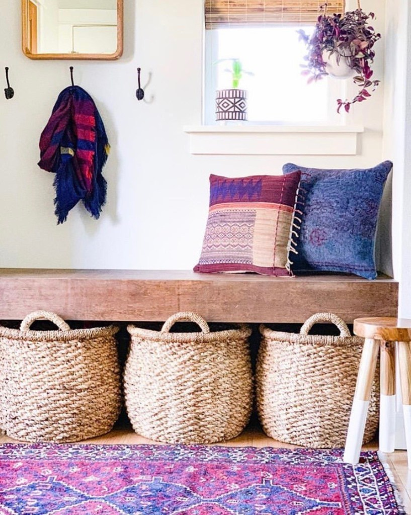 A wooden bench sits above 3 large woven baskets. The bench is topped with blue and purple pillows