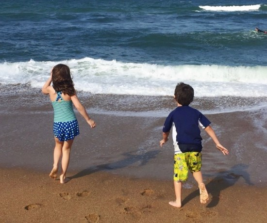 summer break with kids on a beach next to waves