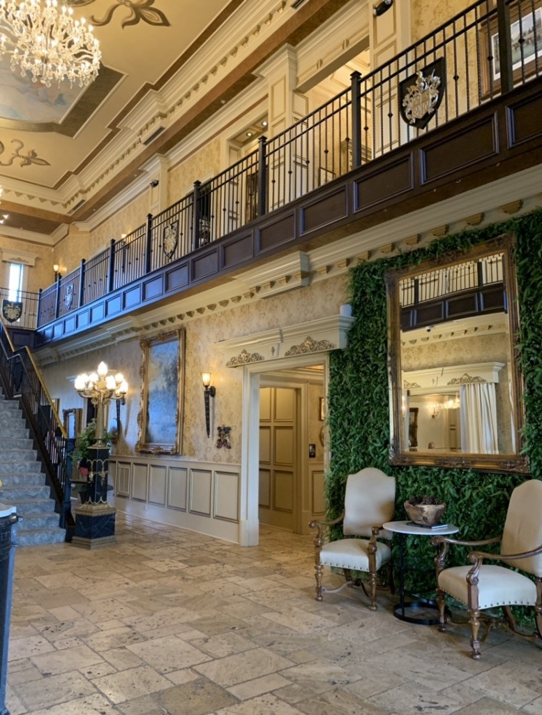 Lobby of a hotel with a view of railing of second floor hallway