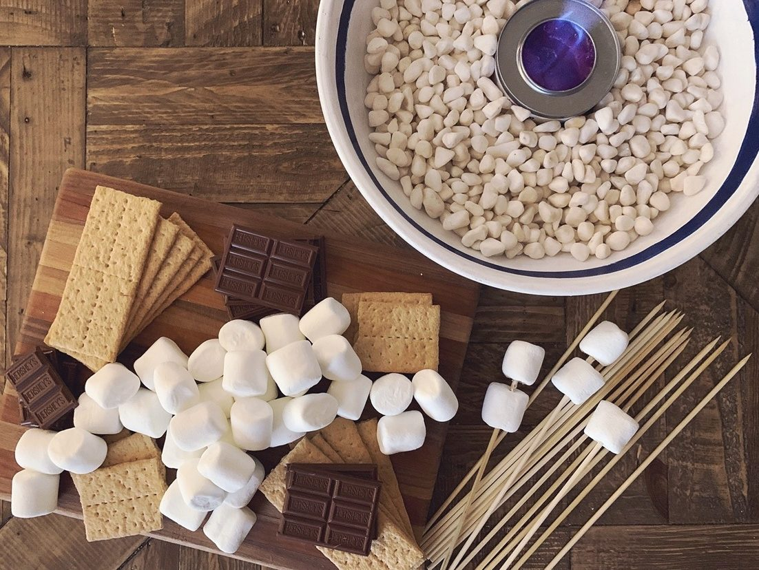 S'mores ingredients arranged on a board with a tabletop fire pit