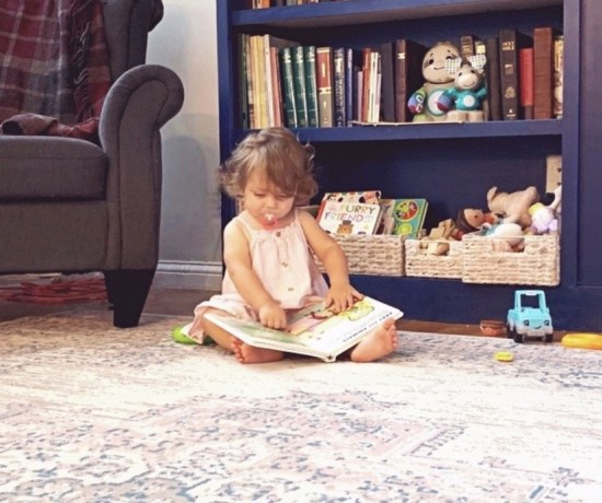A toddler sits on a rug looking at a book for toddlers & babies in front of a bookshelf.