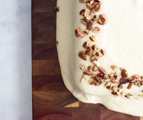 A cake with cream cheese frosting and a border of chopped pecans sits on top of a wooden serving board.