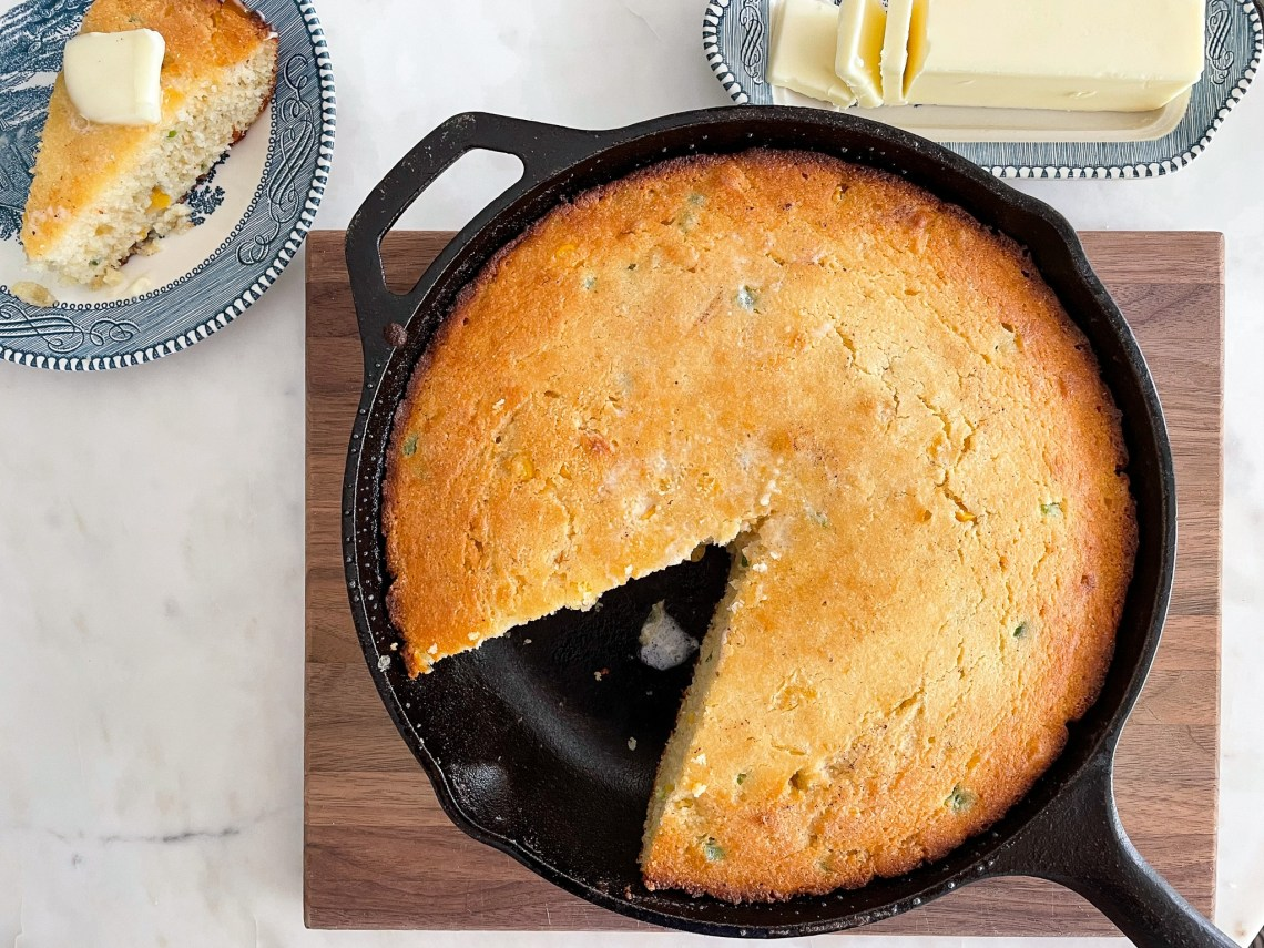 An iron skillet with freshly baked jalapeño cornbread sits on top of a wooden cutting board, next to a butter dish and slice of cornbread.