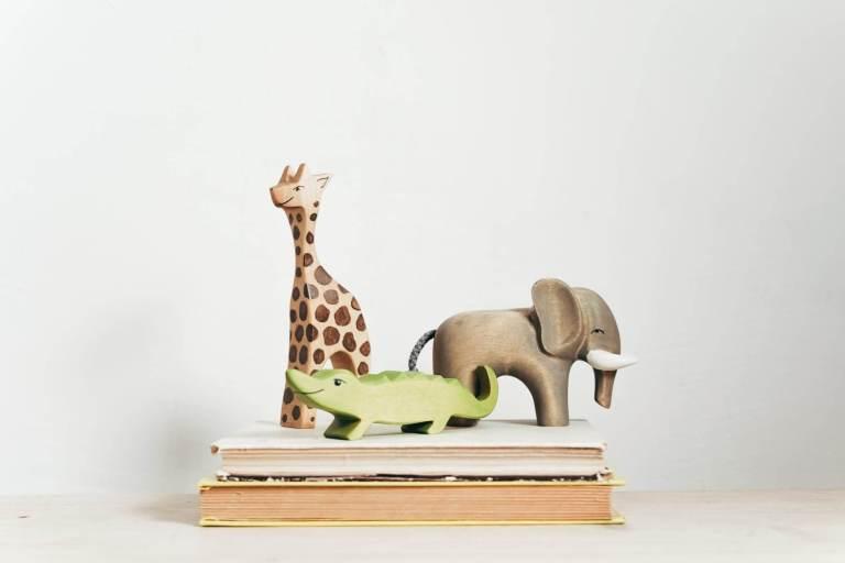 brown and green giraffe figurine on book