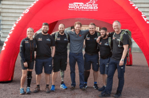 Prince Harry poses with Wounded Warriors at the Walk of Britain.