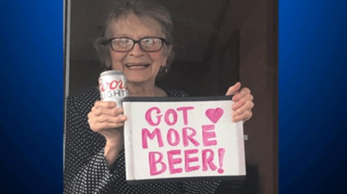 93-year-old Olive Veronesi holds up a new sign standing next to her delivery of 12 cases of beer thanks to the folks at Coors Light.