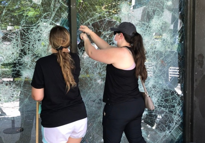 Two women pick out shards of glass from the shattered windows of CNN Center Atlanta.