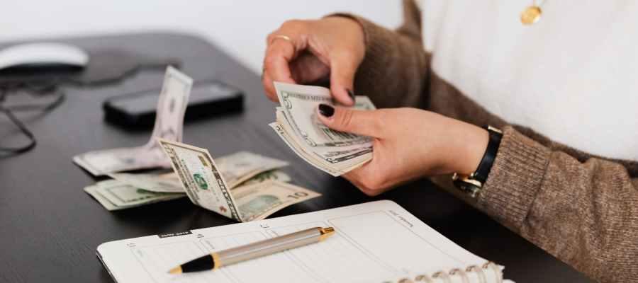 Клерк по начислению заработной платы подсчитывает деньги, сидя за столом