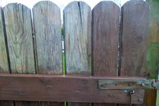 Gartentor Innenansicht: Ein Teil des Tores ist bereits in nussbraun gestrichen. Der andere Teil ist noch hellbeige.