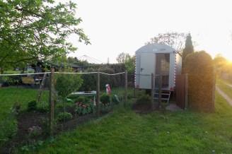 Blick von außerhalb des Gartens auf den Bauwagen nach Süden ausgerichtet vor einer Lebensbaumhecke.