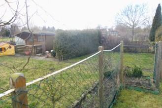 Die Hecke teilt den Garten auf der linken Seite hart in zwei Hälften