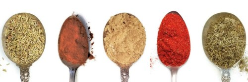 five different spices on spoons