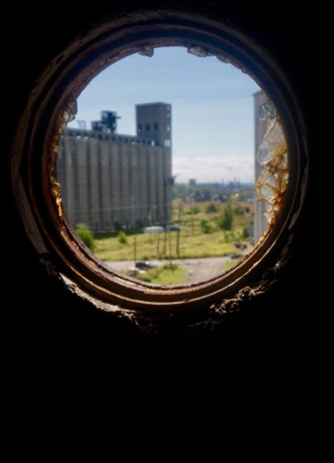 A glimpse out a small window at the other grain silos in Buffalo