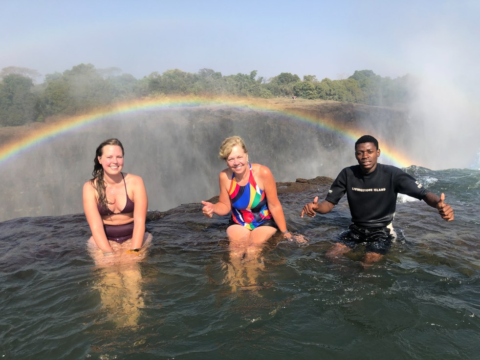 three people sitting under a rainbow at the top of a waterfall