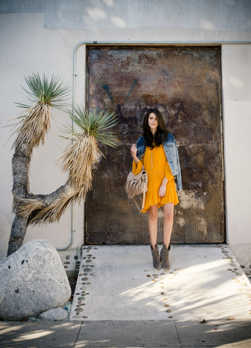 Jackie Roque styling a Zara yellow dress, Proenza Schouler Bag, and Joie boots