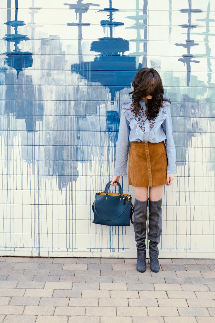 Jackie Roque styling a Chicwish embroidered floral top with a Forever 21 suede button down skirt, Coach Rogue bag and over-the-knee grey boots.