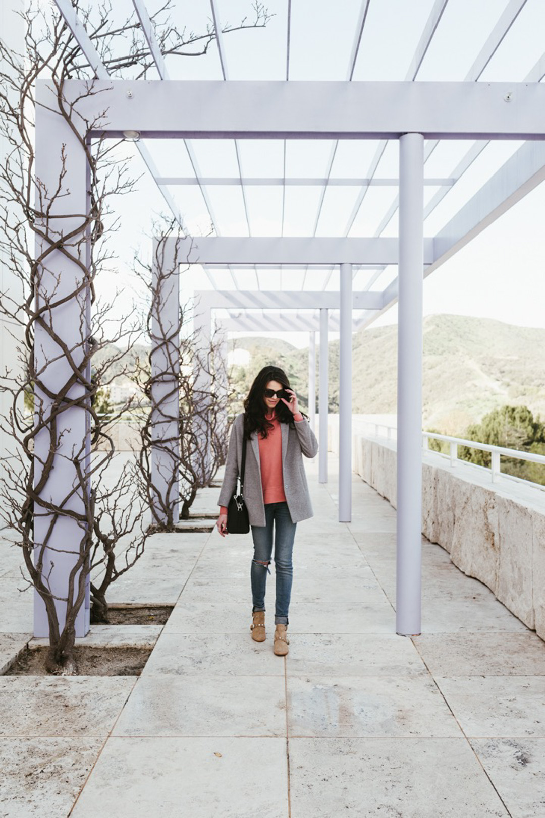 Jackie Roque styling a Madewell sweater, grey wool coat, Rag and Bone ripped jeans, Rebecca Minkoff Abigail Booties and Celine sunglasses at The Getty Museum in LA