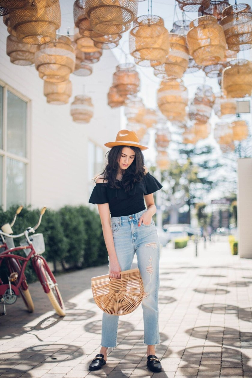 Jackie Roque styling a Aqua off-the-shoulder body suit, Madewell jeans and a Cult Gaia Arc bag.