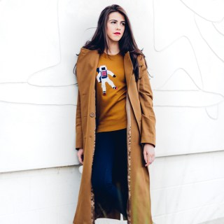 Jackie Roque styling a Lacoste Fall 2017 look with a brown trench coat and astronaut sweater.