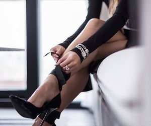 Woman wearing black high heels, black dress, and silver accessoires
